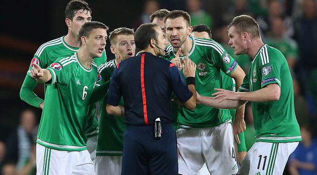 Disbelief: Northern Ireland players surround referee Cuneyt Cakir after he brandished two yellows to Chris Baird (left)