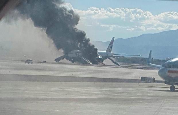Flames could be seen coming from the plane. Pic: Eric Hays via AP.
