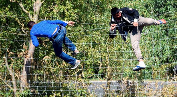 Migrants cross a fence protecting a road after they broke through a police line near a collection point of Roszke village at the Hungarian-Serbian border on September 9, 2015. Some 400-500 migrants on Wednesday broke through police lines in Hungary near the main crossing point from Serbia, AFP reporters at the scene said. AFP PHOTO / ATTILA KISBENEDEKATTILA KISBENEDEK/AFP/Getty Images
