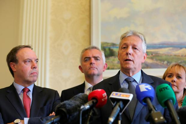 First Minister Peter Robinson at Stormont, Belfast, watched by Nigel Dodds, Johnathan Bell and Michelle Mcilveen, announces that he is standing aside, and the majority of his Democratic Unionist ministers are to resign, with party colleague Arlene Foster to take over as acting First Minister. Niall Carson/PA Wire
