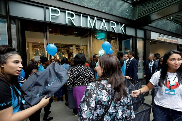 Shoppers are offered bags as they enter a Primark retail store in the Downtown Crossing neighborhood of Boston
