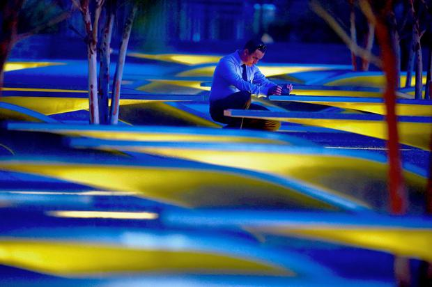 An unidentified man takes photos before sunrise at the National 9/11 Pentagon Memorial September 11, 2015, on the 14th anniversary of the 911 attacks. AFP PHOTO/PAUL J. RICHARDSPAUL J. RICHARDS/AFP/Getty Images