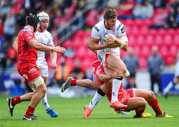 Ulster's Stuart McCloskey is tackled by Scarlets' Regan King. Pic INPHO/Craig Thomas