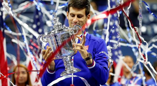 Smile of a champion: Novak Djokovic gets his hands on the US Open trophy after defeating Roger Federer in the final