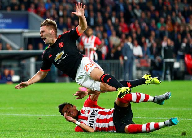 PSV's Hector Moreno, down, tackles Manchester Uniteds Luke Shaw, up, during the Champions League Group B soccer match between PSV and Manchester United at Philips stadium in Eindhoven, Netherlands, Tuesday, Sept. 15, 2015. (AP Photo/Peter Dejong)