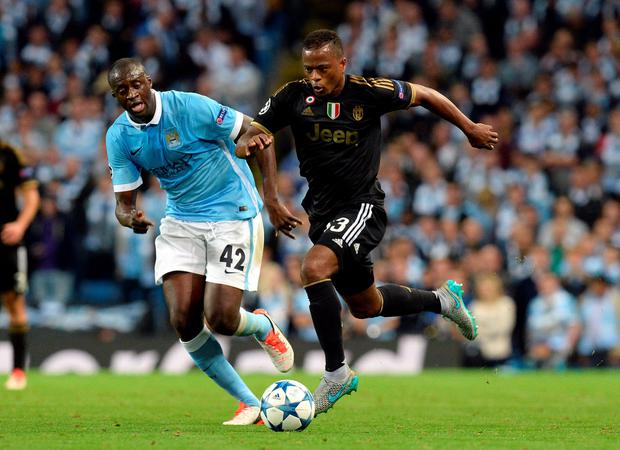 Manchester City's Yaya Toure (left) and Juventus' Patrice Evra battle for the ball during the UEFA Champions League match at the Etihad Stadium, Manchester. Photo: Martin Rickett/PA