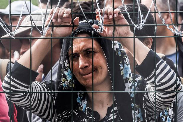 A refugee stands behind a fence at the Hungarian border with Serbia near the town of Horgos on September 16, 2015. AFP/Getty Images