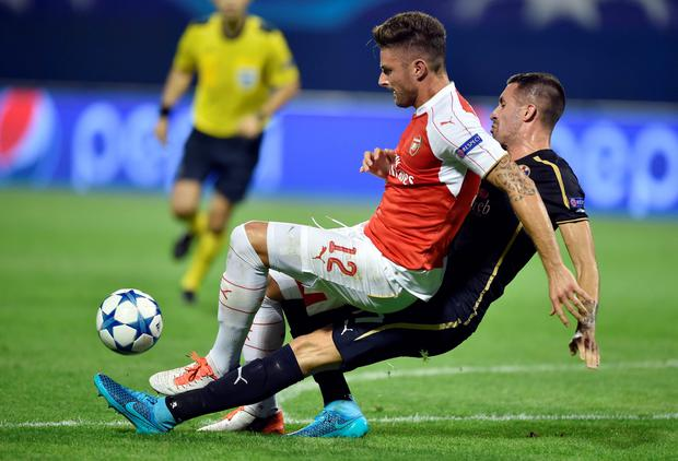 Arsenal's French forward Olivier Giroud (L) vies with Dinamo Zagreb's Macedonian midfielder Arijan Ademi (R) during the UEFA Champions League Group F football match. AFP/Getty Images
