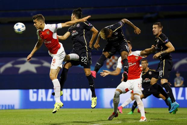Arsenal's Gabriel, left and Zagreb's Leonardo Sigali, 2nd left challenge for he ball during a Champions League Group F soccer match between Dinamo Zagreb and Arsenal at the Maksimir Stadium in Zagreb, Croatia, Wednesday Sept. 16, 2015. (AP Photo/Darko Bandic)