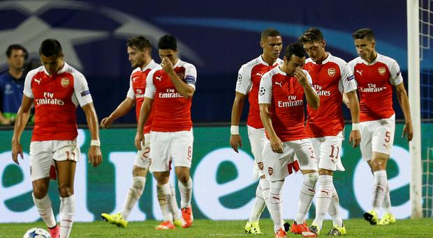 Gunned down: Arsenal players hang their heads in defeat in Zagreb last night