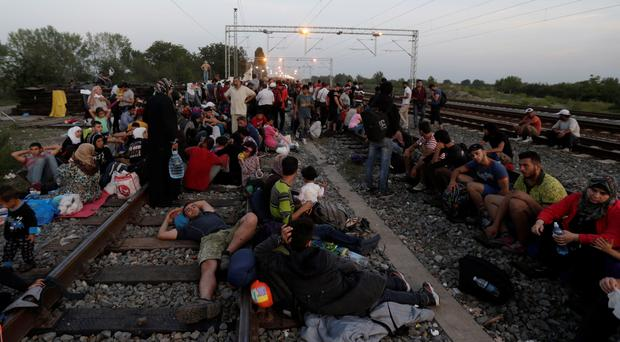 Migrants rest as they wait for a train to arrive at the train station in Tovarnik, Croatia, Friday, Sept. 18, 2015. (AP Photo/Petr David Josek)