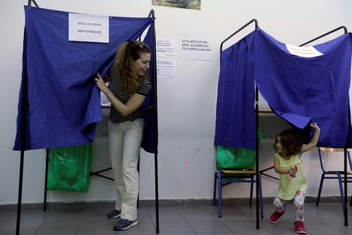 A woman casts her vote as her three-year old daughter plays in an election booth at a polling station in Athens, Sunday, Sept. 20, 2015. (AP Photo/Thanassis Stavrakis)