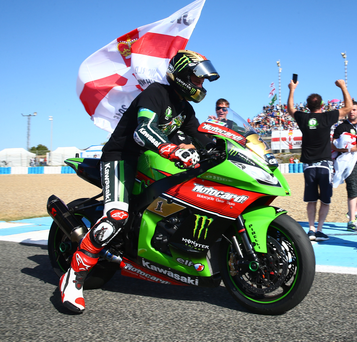 Just champion: Jonathan Rea proudly displays an Ulster flag and celebrates with fans after being crowned World Superbike champion following yesterday's opening race at Jerez