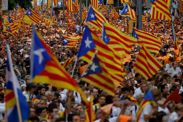 People wave pro-independence Catalan flags, known as the Estelada flag, during a rally calling for the independence of Catalonia, in Barcelona, Spain, Friday, Sept. 11, 2015. (AP Photo/Francisco Seco)