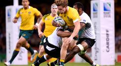 Australia's Michael Hooper (centre) is tackled by Fiji's Peceli Yato and Akapusi Qera (right) during the Rugby World Cup match at the Millennium Stadium, Cardiff