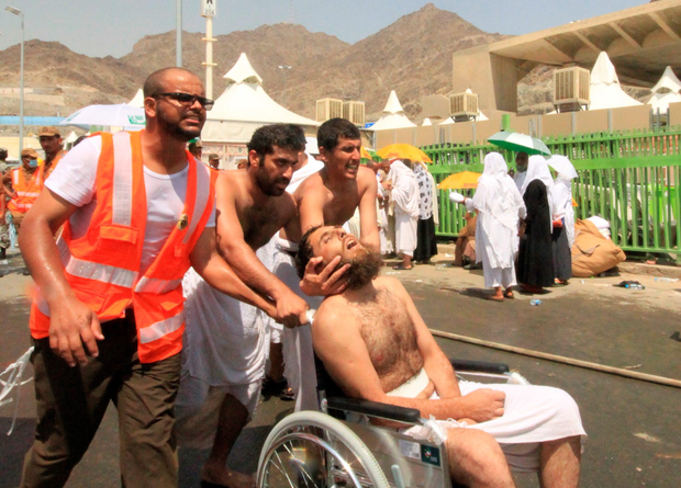 Saudi emergency personnel and Hajj pilgrims push a wounded person in a wheelchair at the site where at least 717 were killed and hundreds wounded in a stampede in Mina, near the holy city of Mecca. AFP PHOTO / STRSTR/AFP/Getty Images