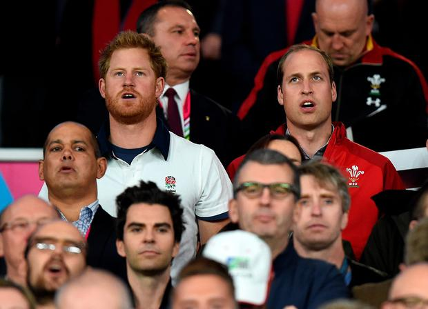 Prince Harry and the Duke of Cambridge sing the National Anthem during the Rugby World Cup match at Twickenham Stadium, London.