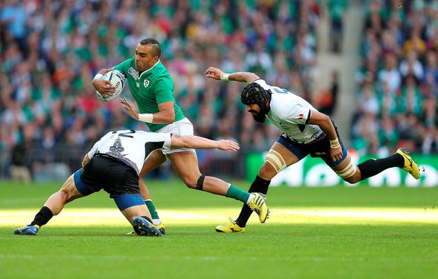 Ireland's Simon Zebo (centre) is tackled by Romania's Csaba Gal (left) and Viorel Lucaci (right) during the Rugby World Cup match at Wembley Stadium, London. David Davies/PA Wire.