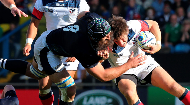 Hitting hard: Alan MacGinty of USA is tackled by Josh Strauss during their match at Elland Road