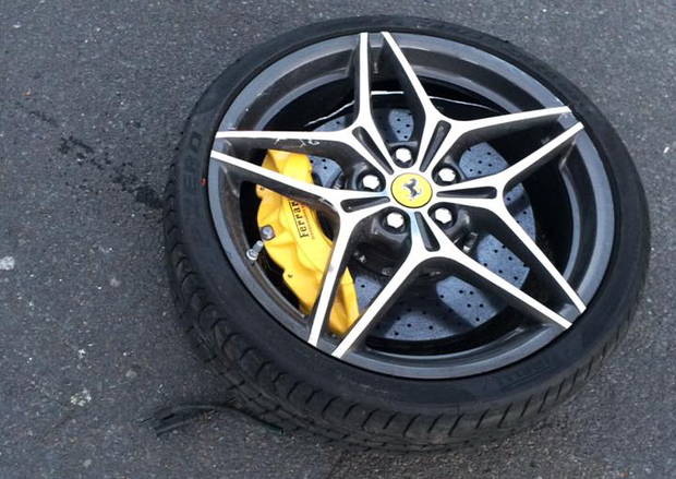 Ferrari California T wheel, tyre, brake caliper and disc lying on the road. Photograph by Paul Synnott