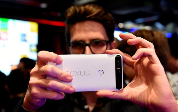 A member of the media takes a photo of with a model of the new Nexus 6P during the launch event at Google HQ in London.