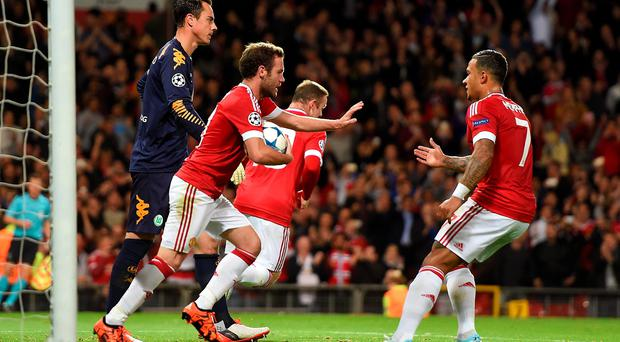 Manchester United's Juan Mata carries the ball back to the centre circle after scoring his side's first goal from the penalty spot during the UEFA Champions League Group B match at Old Trafford, Manchester.