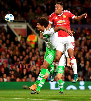 Manchester United's Anthony Martial directs a header on goal under pressure from VfL Wolfburg's Dante during the UEFA Champions League Group B match at Old Trafford, Manchester. PRESS ASSOCIATION Photo. Picture date: Wednesday September 30, 2015. See PA story SOCCER Man Utd. Photo credit should read: Martin Rickett/PA Wire.