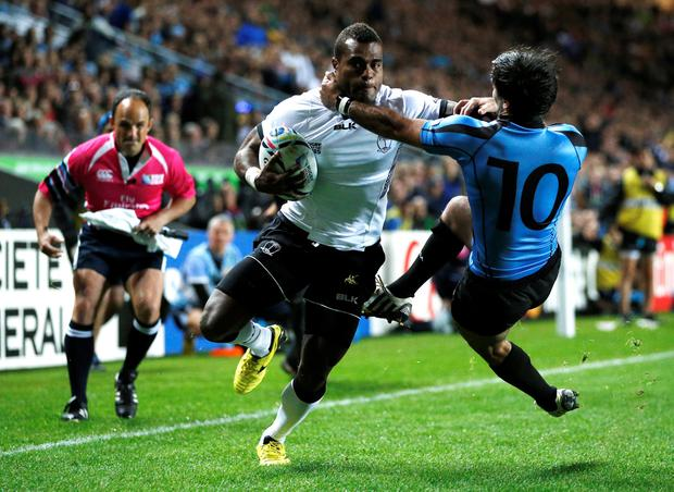 Fiji's scrum half Nemia Kenatale (C) hands off Uruguary's fly half Alejo Duran to score a try during a Pool A match of the 2015 Rugby World Cup between Fiji and Uruguay at Stadium MK in Milton Keynes, north of London, on October 6, 2015. Getty Images