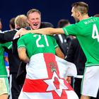 Northern Ireland's manager Micheal O'Neill (C) celebrates with Northern Ireland's Josh Magennis (L) and Gareth McAuley (R) after winning the UEFA Euro 2016 qualifying Group F football match between Northern Ireland and Greece at Windsor Park in Belfast, Northern Ireland, on October 8, 2015. AFP PHOTO / PAUL FAITHPAUL FAITH/AFP/Getty Images