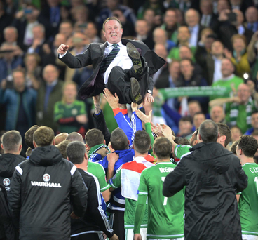 Northern Ireland manager Michael O'Neill is thrown in the air by his players