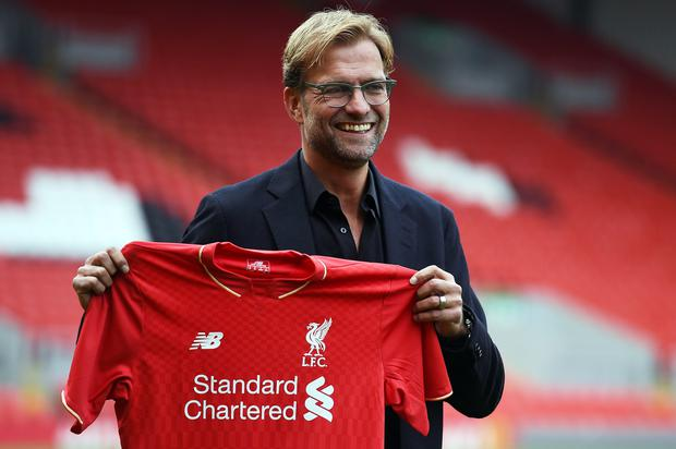 Liverpool's new German manager Jurgen Klopp poses with a team jersey after a press conference to announce his new appointment at Anfield in Liverpool, northwest England, on October 9, 2015. AFP/Getty Images