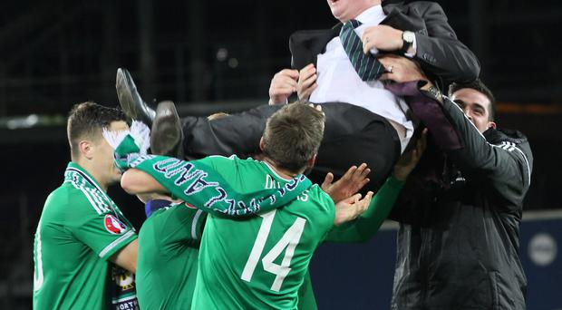 Give us a lift: Northern Ireland boss Michael O'Neill is given the bumps by his jubilant players