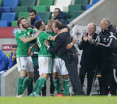 We've done it: Northern Ireland boss Michael O'Neill is mobbed by the players after the team clinched qualification for Euro 2016 on Thursday