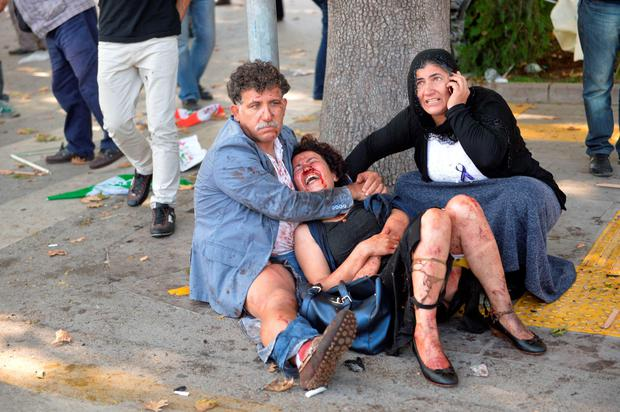 An injured woman is comforted following an explosion at the main train station in Turkey's capital Ankara, on October 10, 2015. AFP PHOTO / ADEM ALTANADEM ALTAN/AFP/Getty Images