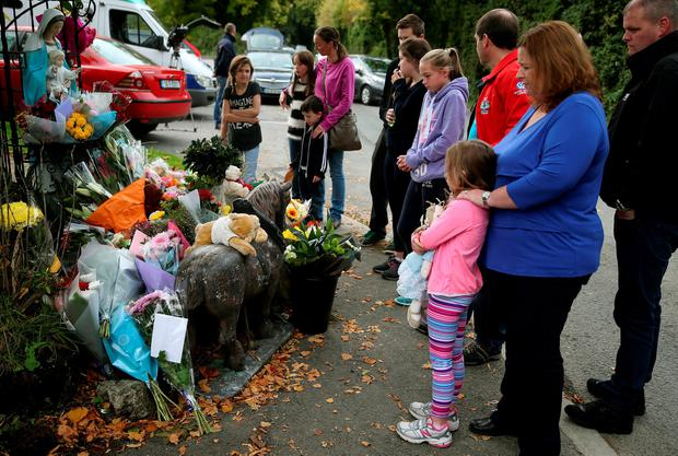 People gather as toys and flowers are left at a halting site for travellers in Carrickmines, south Dublin, where 10 people from two families, including a mother, father and a five-month-old baby, were killed. Photo: Brian Lawless/PA Wire