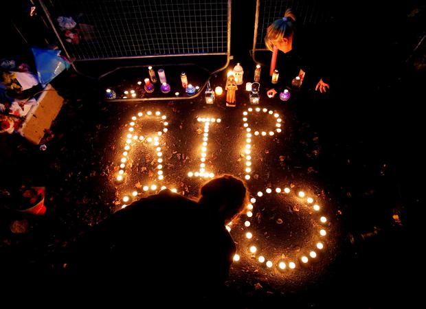Members of the travelling community at a candlelit vigil outside a halting site for travellers in Carrickmines, south Dublin, where ten people from two families, including a mother, father and a five-month-old baby, were killed in a fire at the weekend. PA