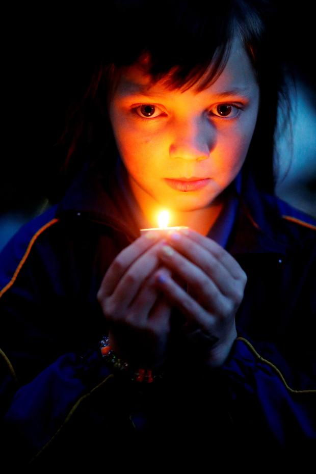 A member of the travelling community at a candlelit vigil outside a halting site for travellers in Carrickmines, south Dublin, where ten people from two families, including a mother, father and a five-month-old baby, were killed in a fire at the weekend. PA
