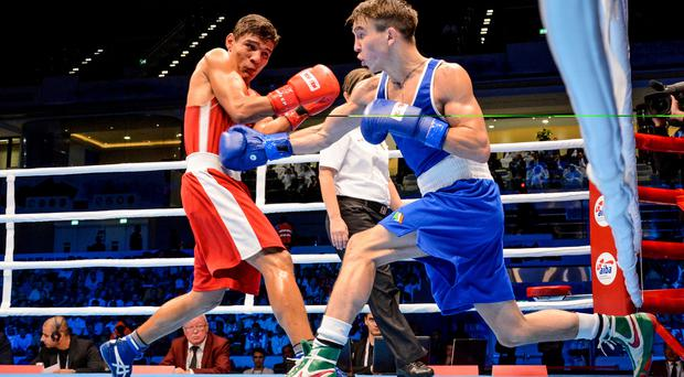 Global glory: Michael Conlan (right) on way to making history with World title victory over Murodjon Akhmadaliev in Doha