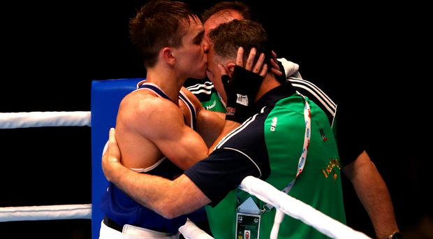 Sealed with a kiss: New World king Michael Conlan thanks coach Billy Walsh as fellow coach Zaur Antia looks on
