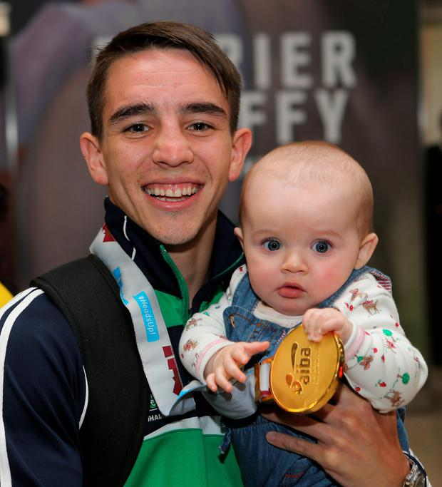 Ireland's Michael Conlan with his daughter Luisne as he returns to Dublin Airport after winning gold in the AIBA World Elite Championships in Doha.
