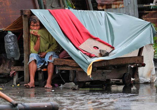 A Filipino man sits inside his makeshift home as strong winds and rains caused by Typhoon Koppu hits the coastal town of Navotas, north of Manila. (AP Photo/Aaron Favila)