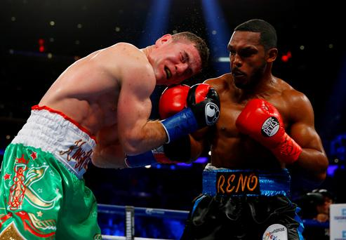 Harsh lesson: Eamonn O'Kane takes another blow from Tureano Johnson during their clash in New York