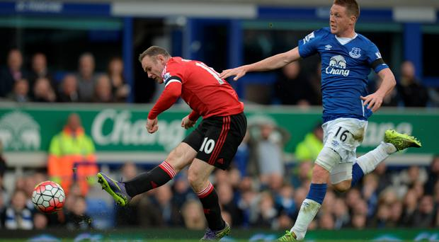 Fired up: Wayne Rooney scores United's third goal despite pressure from Everton's James McCarthy