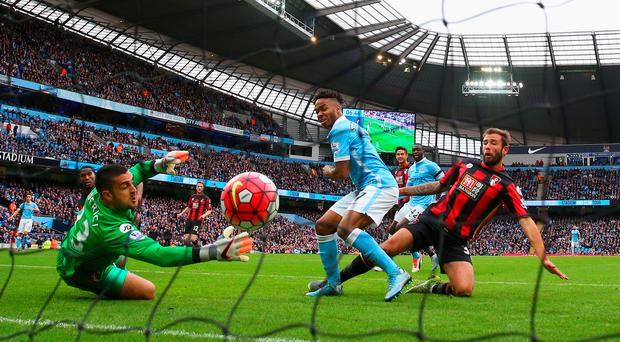 Net gains: Raheem Sterling pokes home the first goal of his hat-trick against Bournemouth at the Etihad Stadium