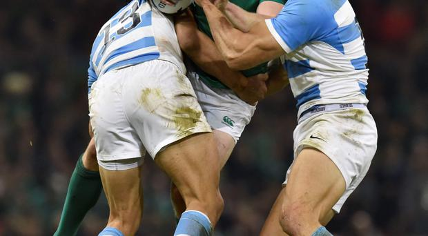 Sandwiched: Keith Earls is tackled by two Argentinian defenders