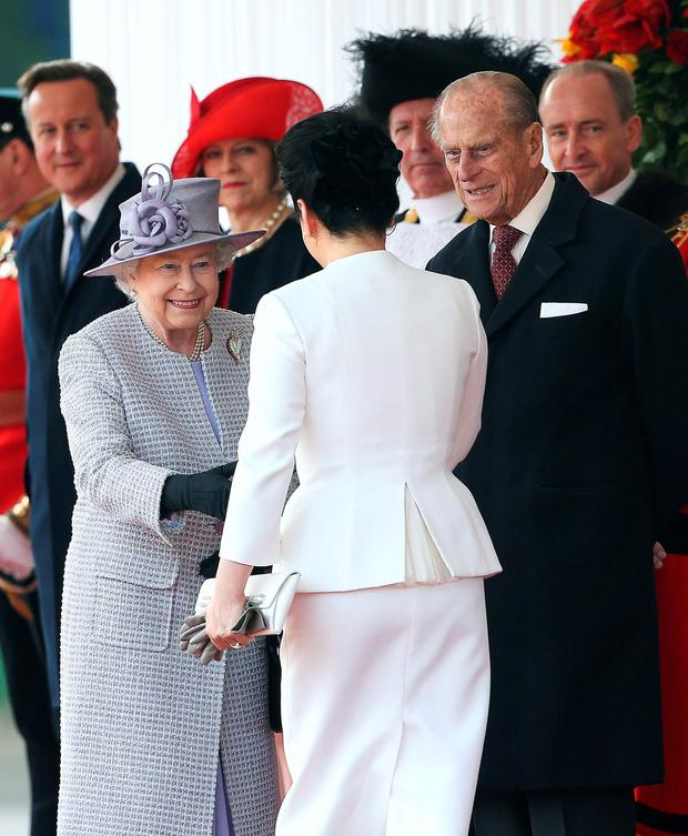 Britain's Queen Elizabeth II (L) shakes hands with China's First Lady Peng Liyuan (C) as Britain's Prince Philip, Duke of Edinburgh (2nd R) looks on at the royal pavilion on Horse Guards Parade in central London on October 20, 2015, during the Chinese president's ceremonial welcome on the first official day of a state visit. Chinese President Xi Jinping arrived for a four-day state visit as the government of Prime Minister David Cameron seeks stronger trade ties with the world's second-largest economy. AFP PHOTO / POOL / CHRIS JACKSONChris Jackson/AFP/Getty Images