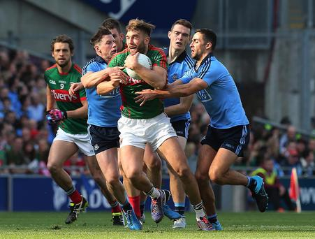 Clash of the giants: Three Dublin men do their best to get to grips with Mayo's bruising Aidan O'Shea