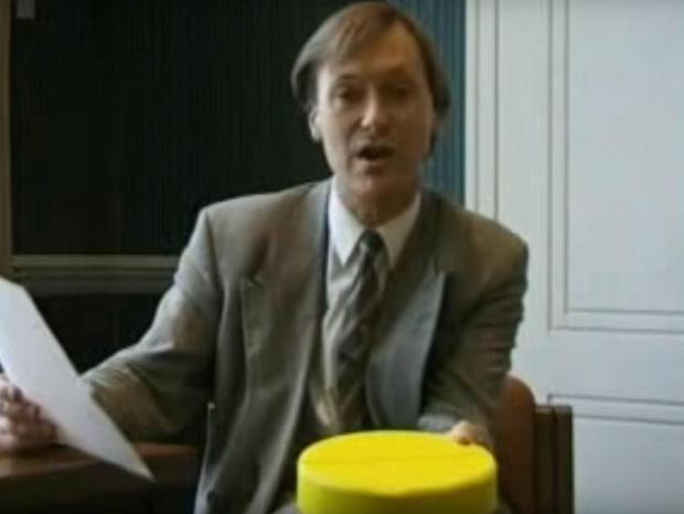 David Amess holds a piece of 'Cake' that he described as 'a big yellow death bullet'