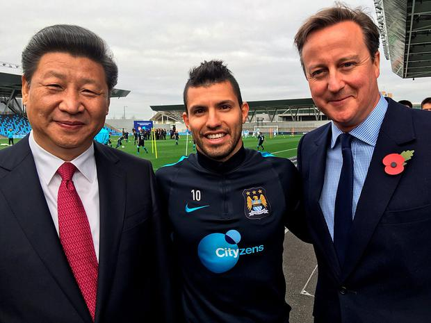 Handout photo dated 23/10/15 provided by MCFC of (from left to right) Chinese President Xi Jinping, Manchester City's Sergio Aguero and Prime Minister David Cameron during a visit to the City Football Academy in Manchester. PA