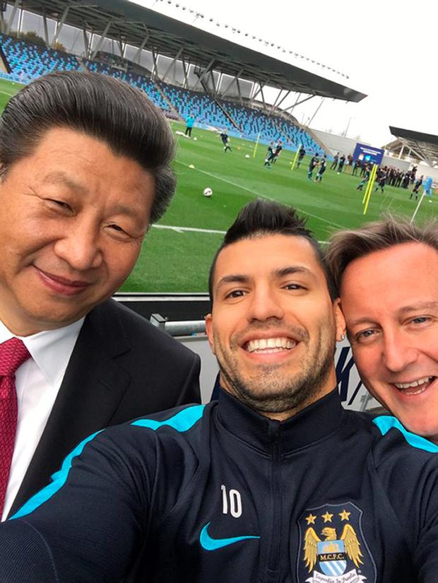 Handout photo issued Manchester City Football Club of the striker Sergio Aguero taking a selfie with Chinese President Xi Jinping and Prime Minister David Cameron as they visited the City Football Academy in Manchester on the last day of the state visit to the UK. PA